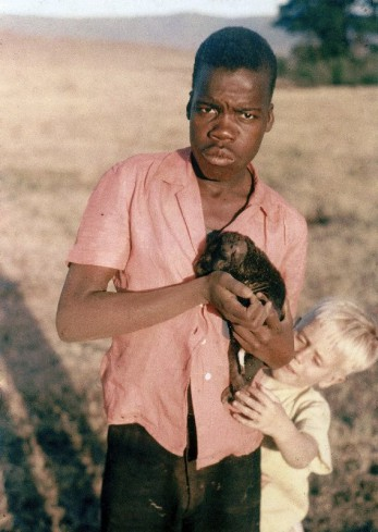 Kimwaga and I in Tanganyika, around 1957. He's warily holding a hyena cub, which may have become one of our menagerie of temporary pets.