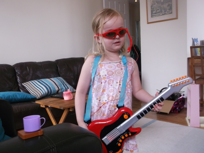 Future rock star tries out her  first guitar